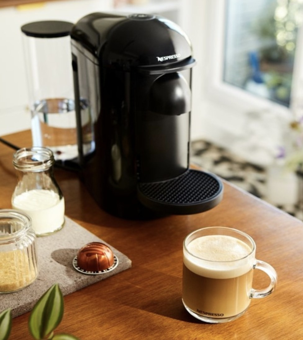 A Nespresso with a mug next to it with a latté inside