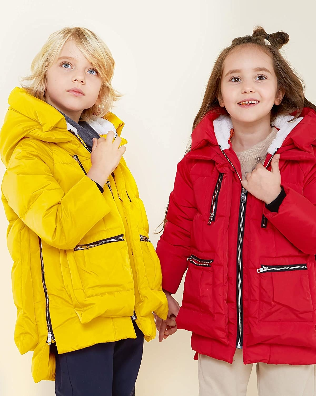 Two kids, one in the yellow coat, one in the red