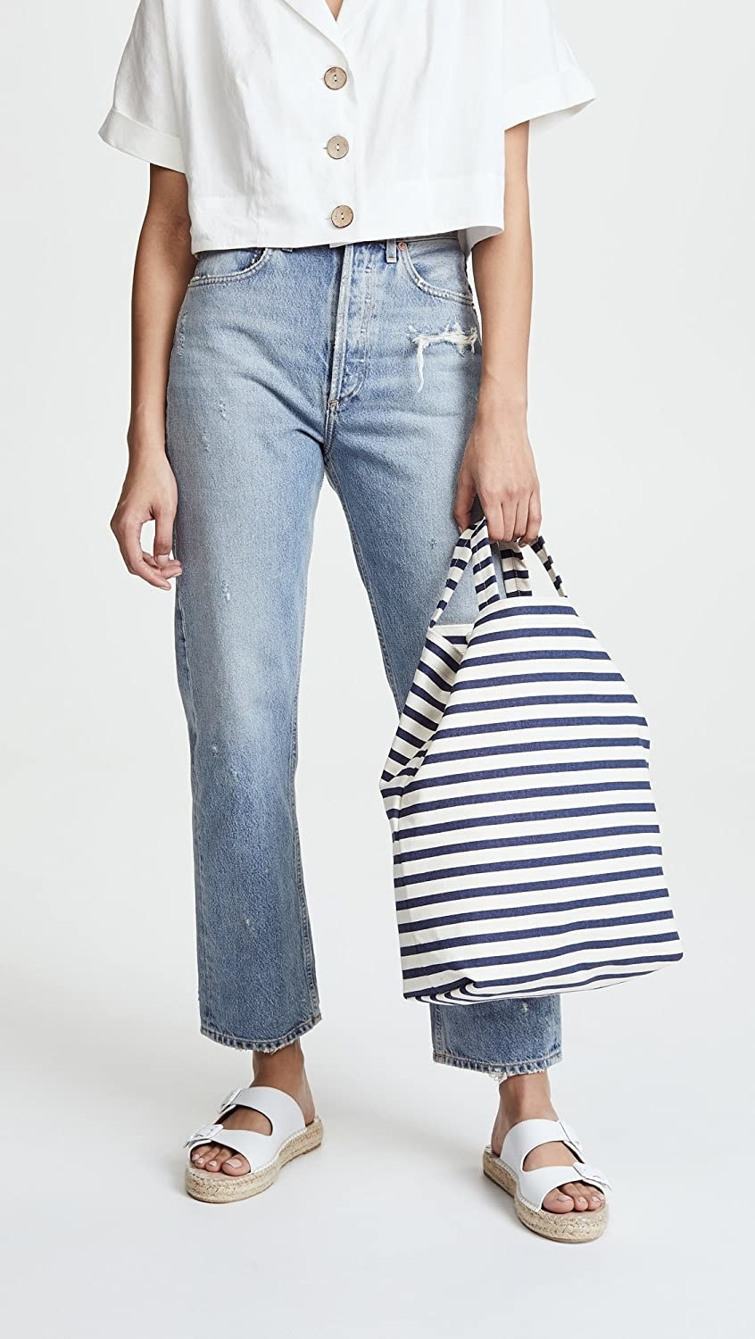 Model carrying the blue and white striped bag