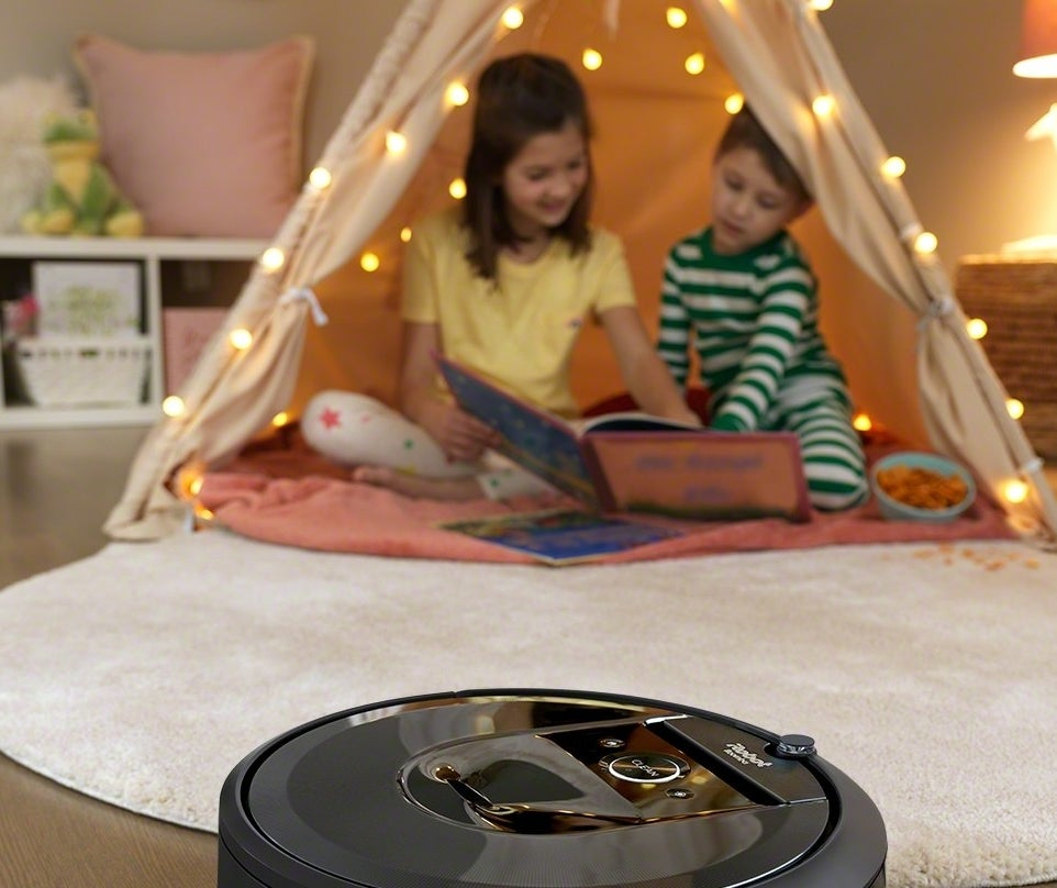 A Roomba sweeping a child's room with two children in a tent behind it