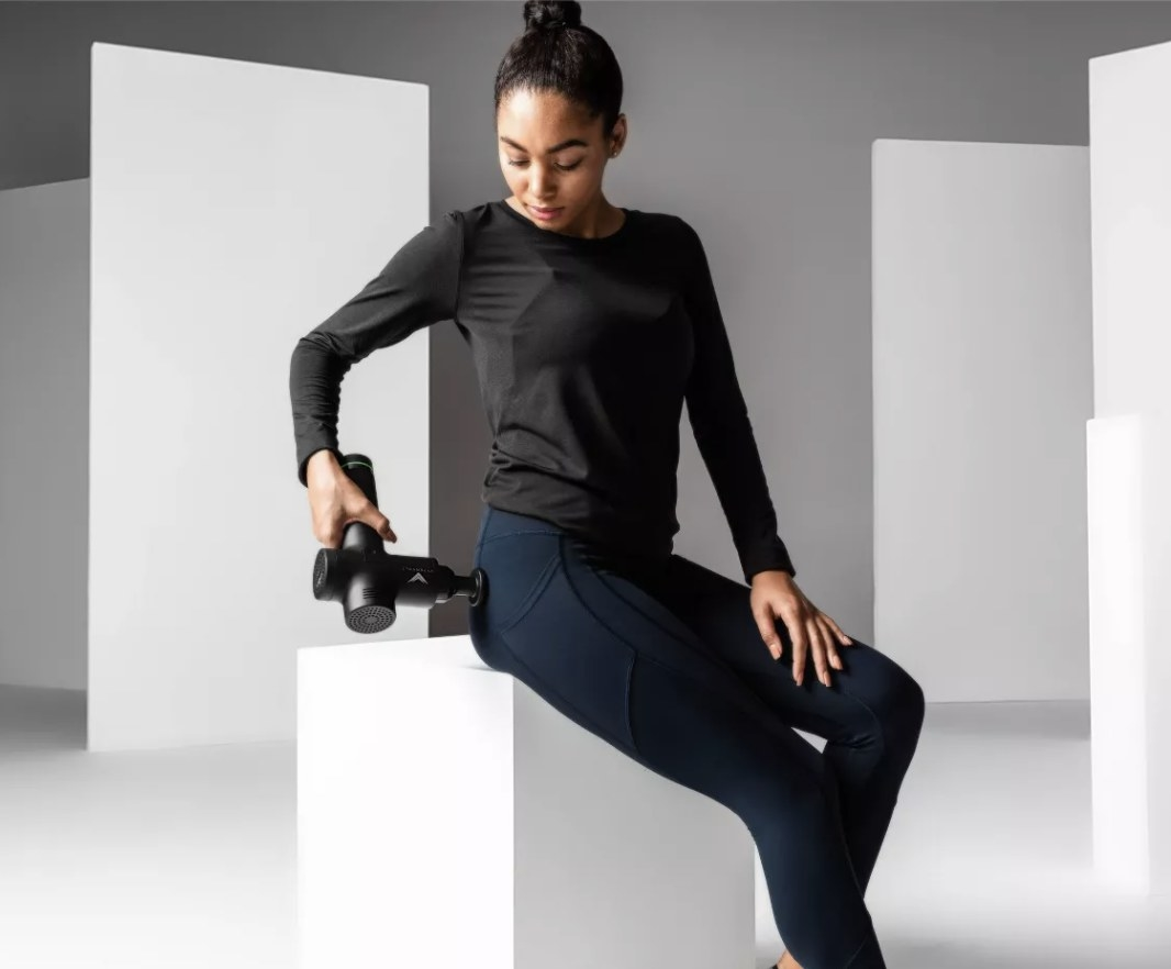 Model is using a black body massager on her glutes