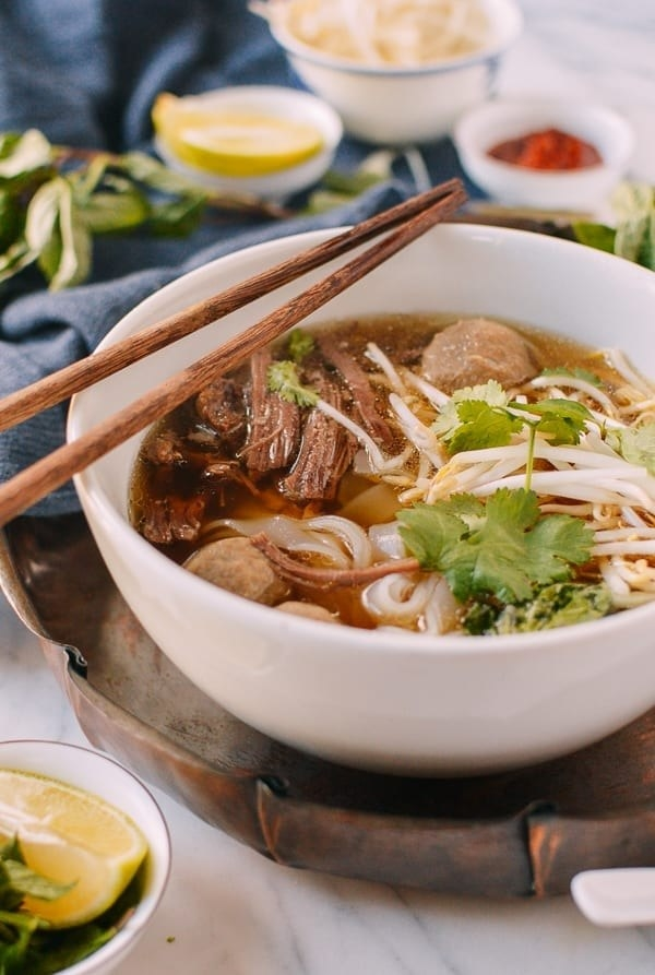 Beef pho with rice noodles and fresh cilantro in a bowl.