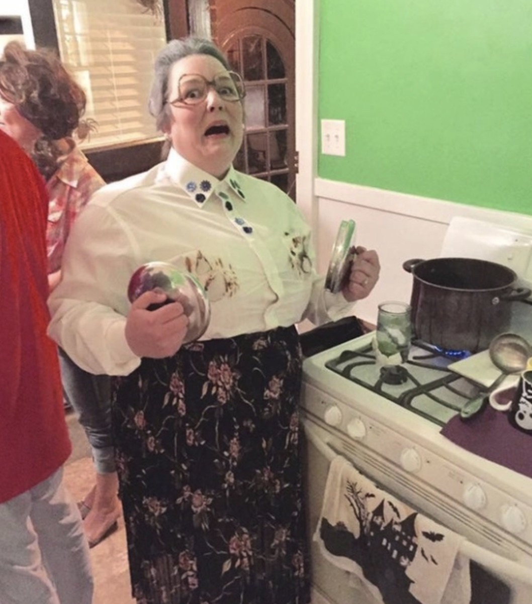 Someone dressed as Mrs. Doubtfire, holding two pan lids over their burnt shirt