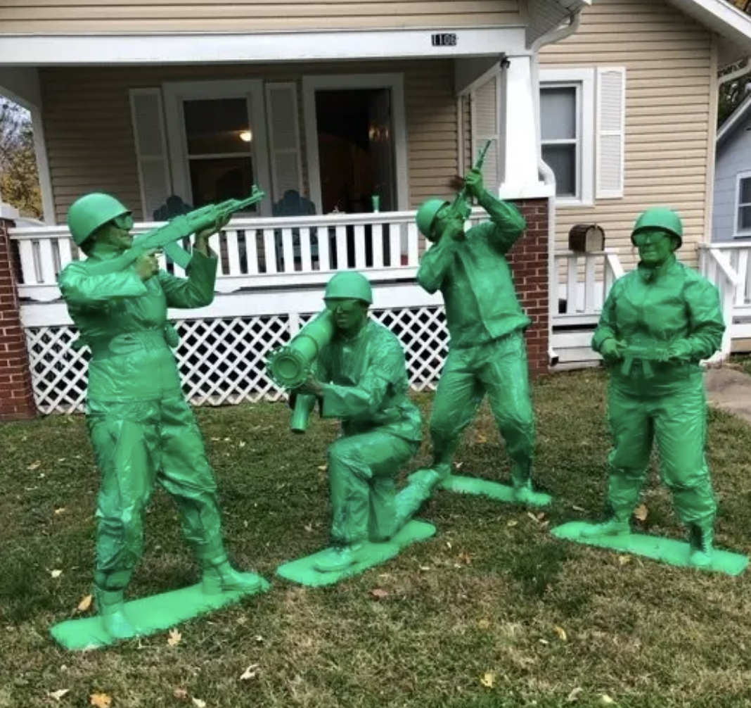 Four people painted green and posing as toy soldier toys