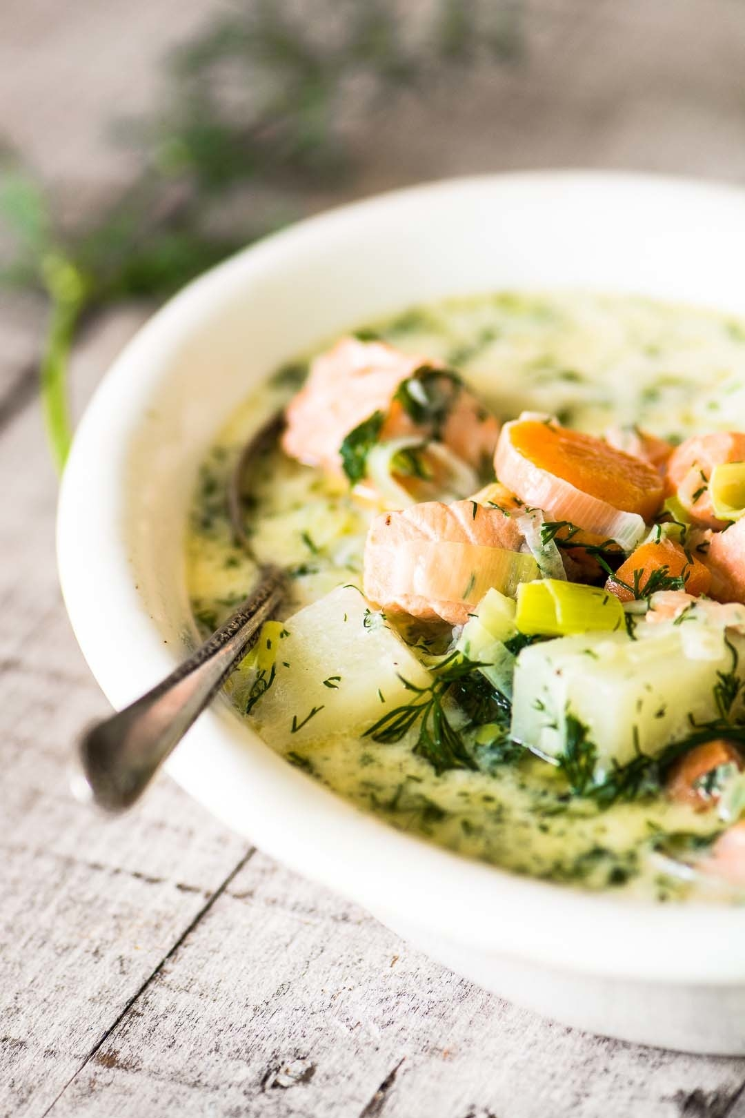 A bowl of creamy chowder with pieces of salmon, potatoes, and fresh dill.