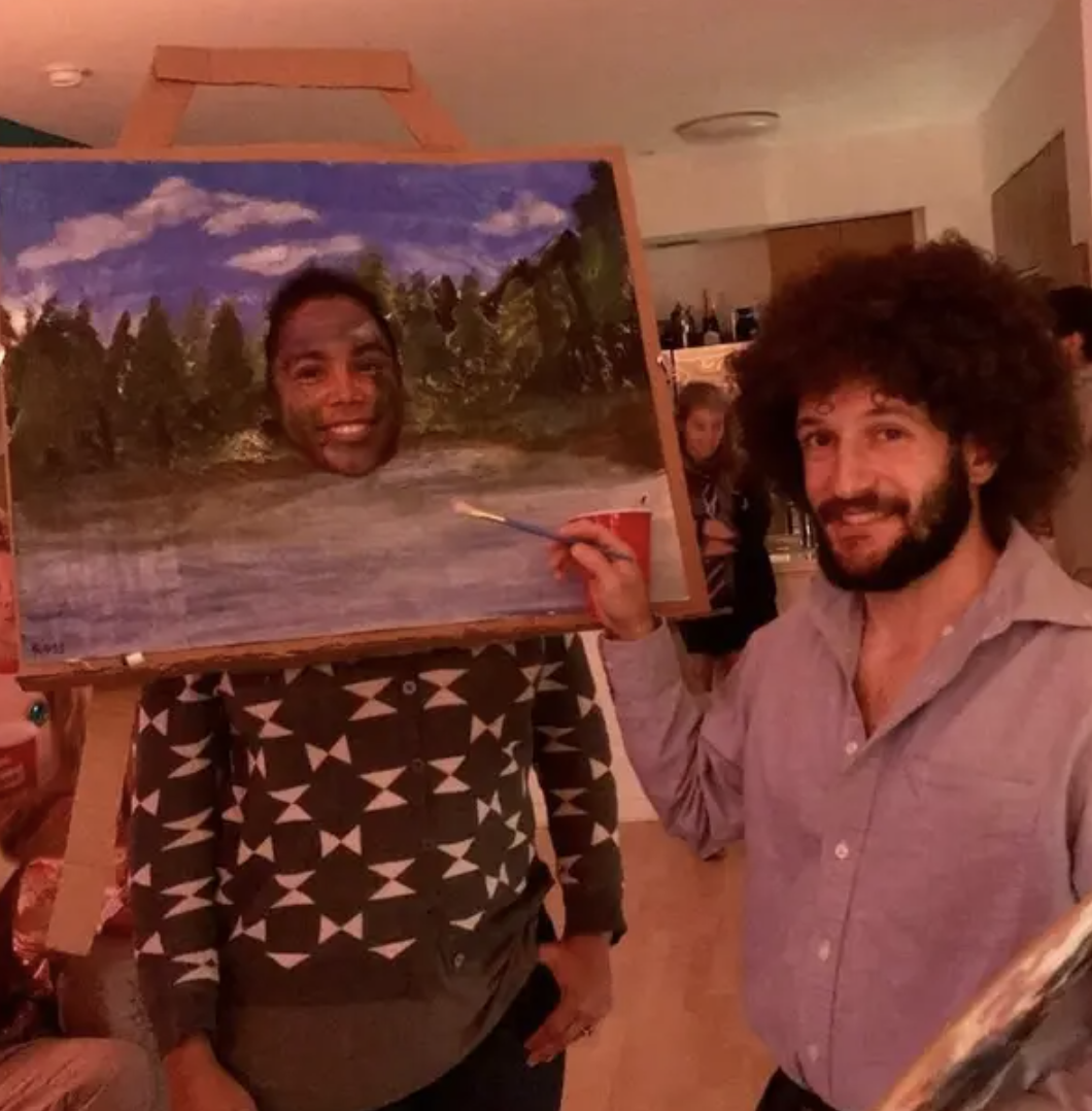 Someone dressed as Bob Ross, and another dressed as a painting of nature with a hole cut out in the middle where their face is