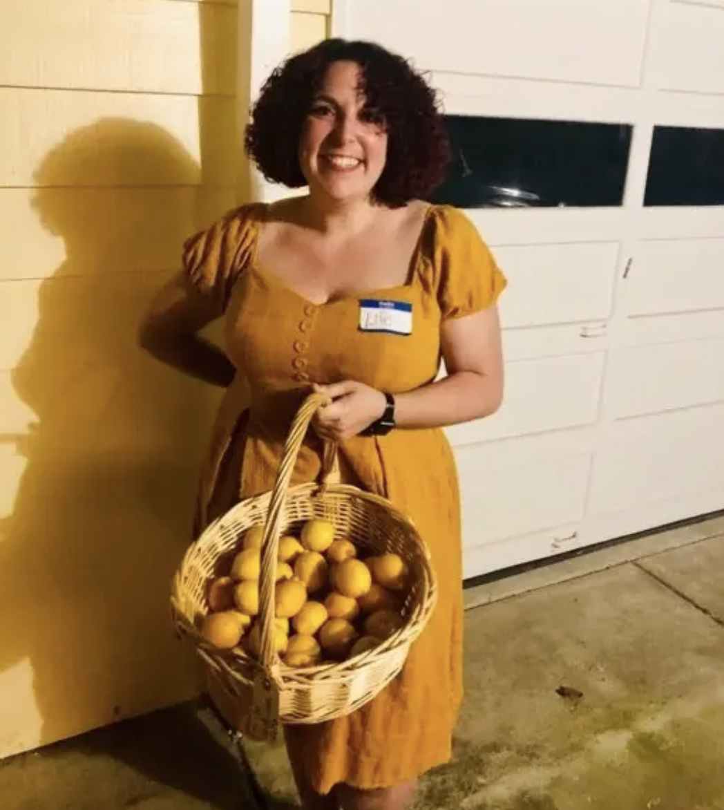 "Someone dressed in all yellow, with a ""Life"" name tag, holding a basket of lemons"