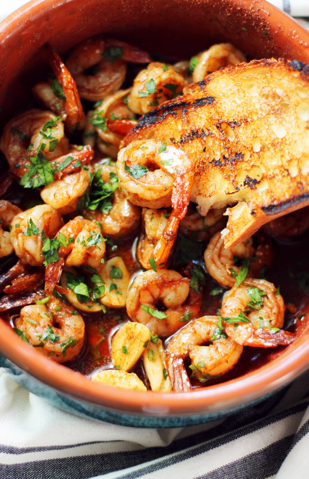 A ceramic bowl filled with shrimp in garlic sauce with fresh herbs and bread on top.