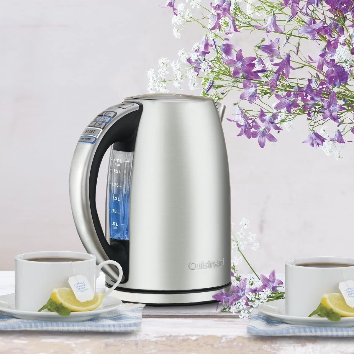 A kettle filled with water beside two cups of tea