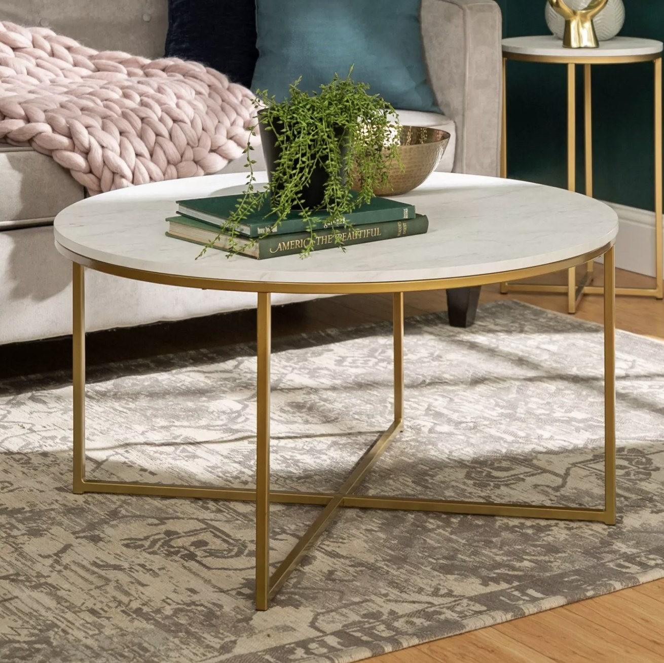 A round white coffee table with gold accents in a living room
