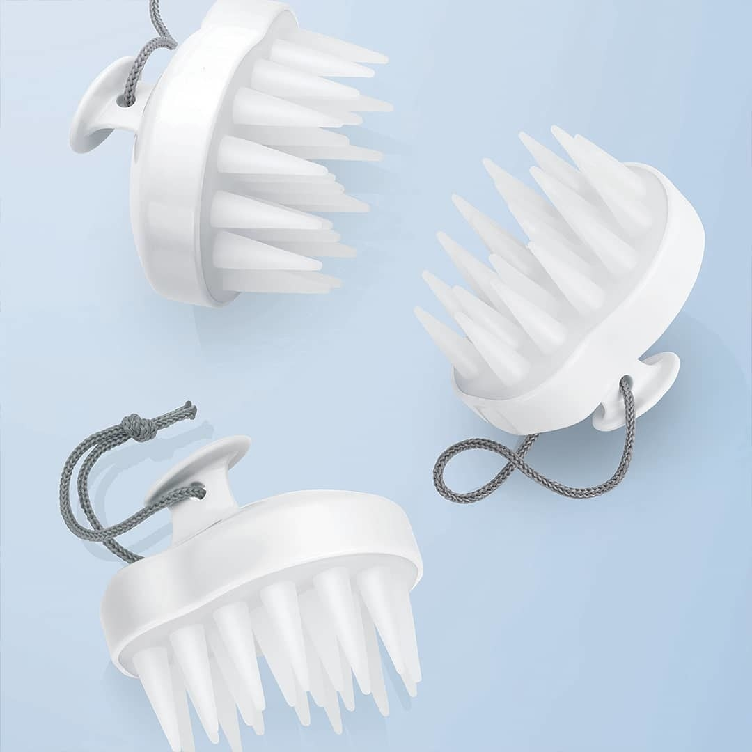 A trio of scalp brushes scattered on a muted background