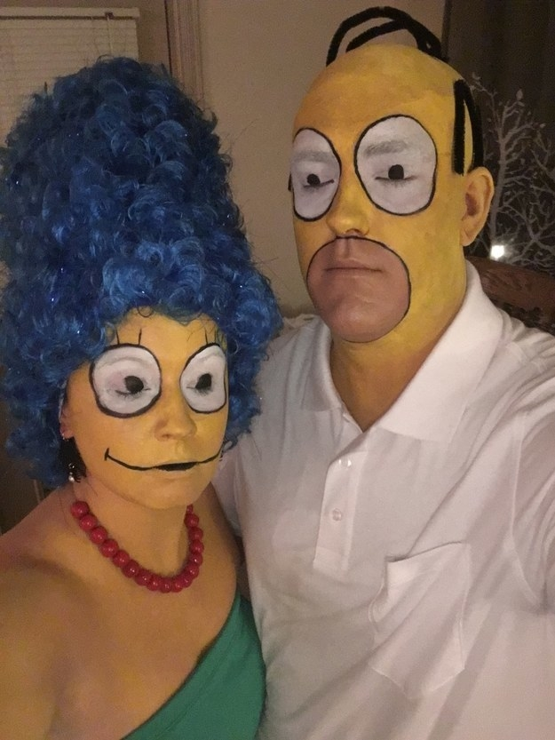 Two people with their faces painted to make them look like the cartoon versions of Marge and Homer.