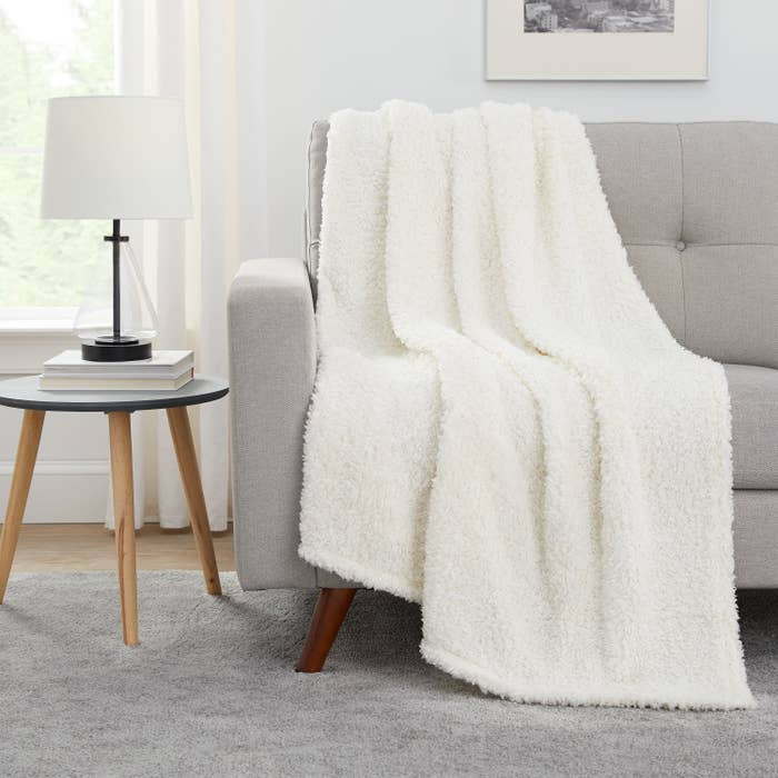 The throw blanket in white draped over a couch