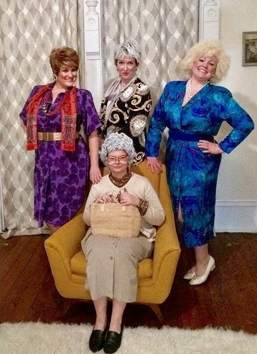 Four women dressed in printed vintage '80s outfits with shoulder pads, appearing to look like old women. They all have short wigs on.