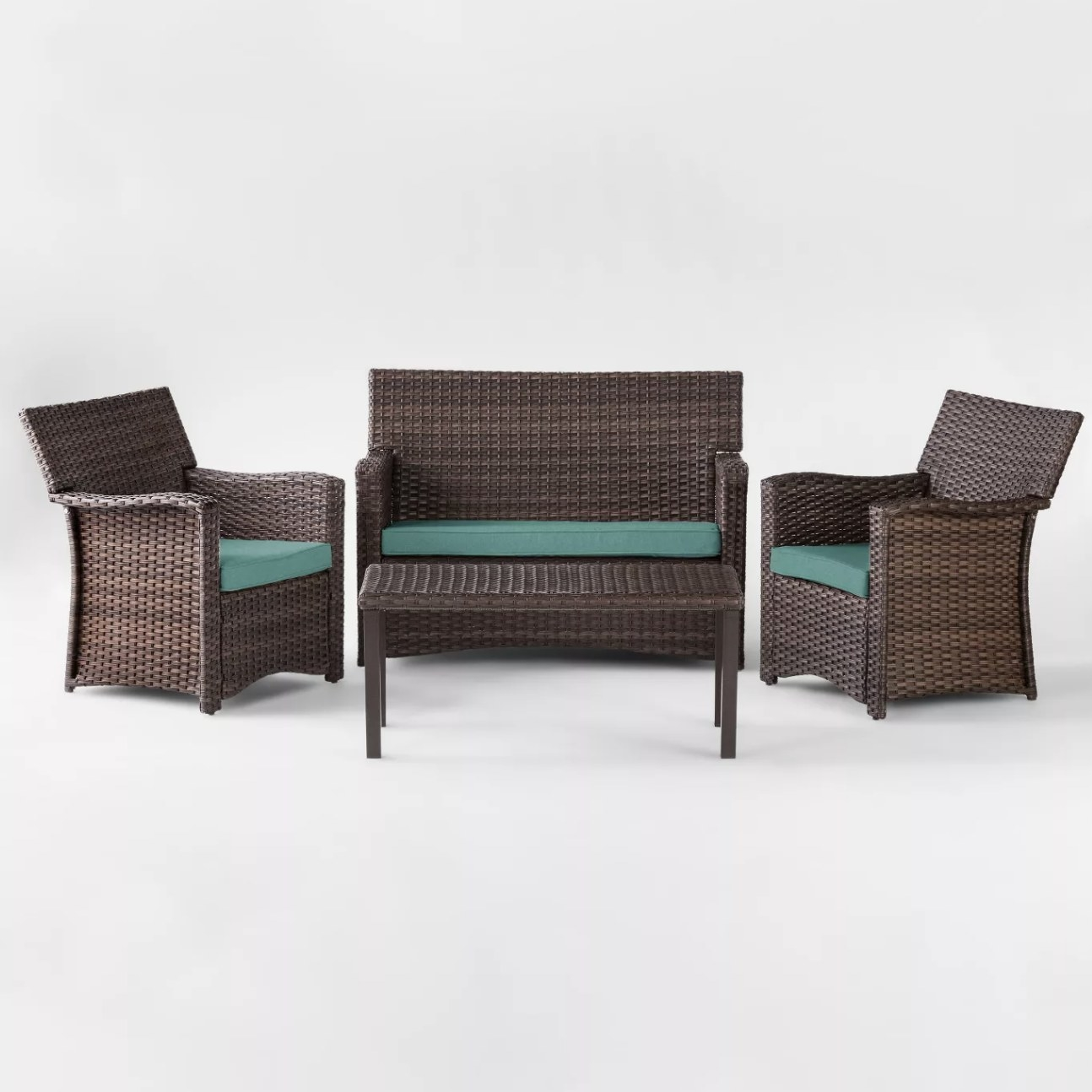 A four-piece dark wood-colored wicker set with three seats and a coffee table and blue cushions