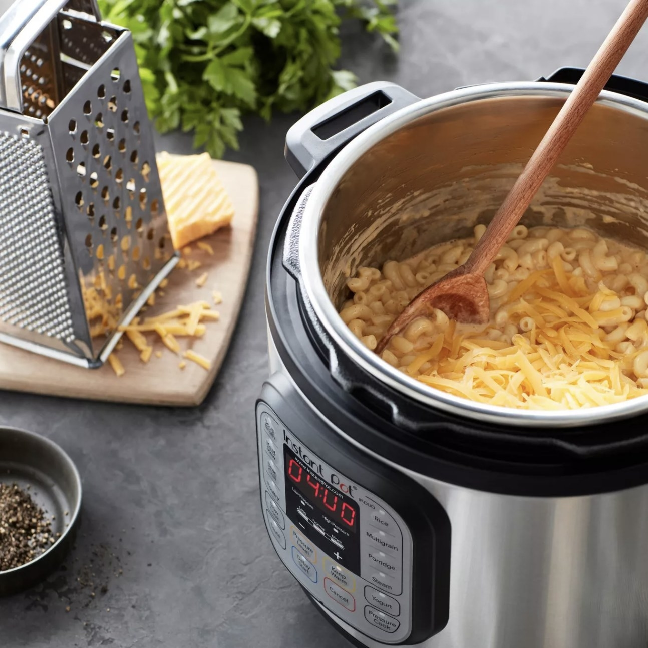 The instant pot with the lid off showing mac and cheese cooked inside