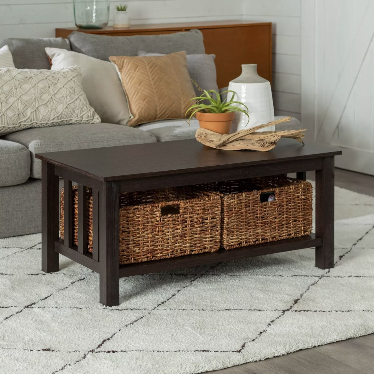 A dark wood coffee table with wicker basket totes underneath in a living room