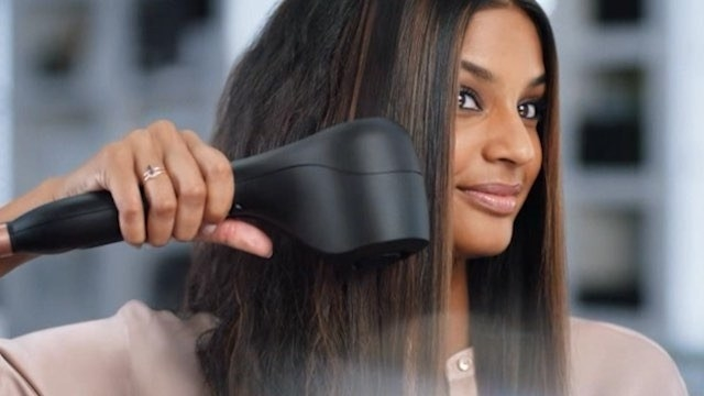 A smiling person uses the tool to smooth out their hair