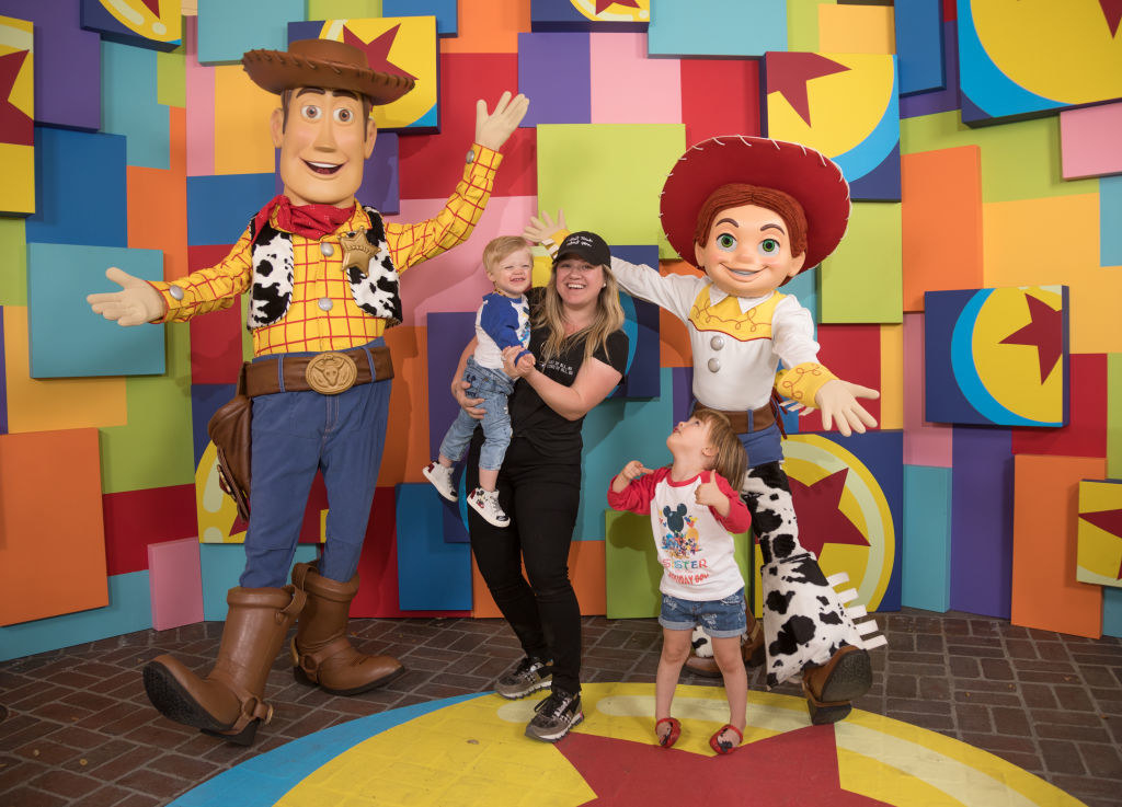 Kelly and her youngest children next to a giant Woody and Jessie from Toy Story