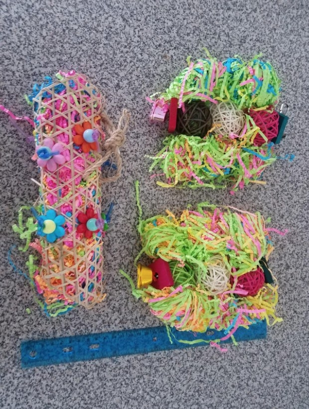 Three colorful shredded paper bird toys