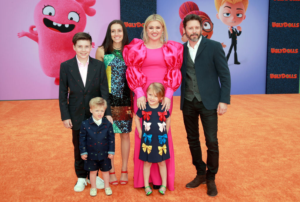 Kelly and Brandon smiling with their four children