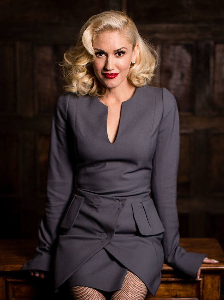 Gwen grinning while leaning against a desk