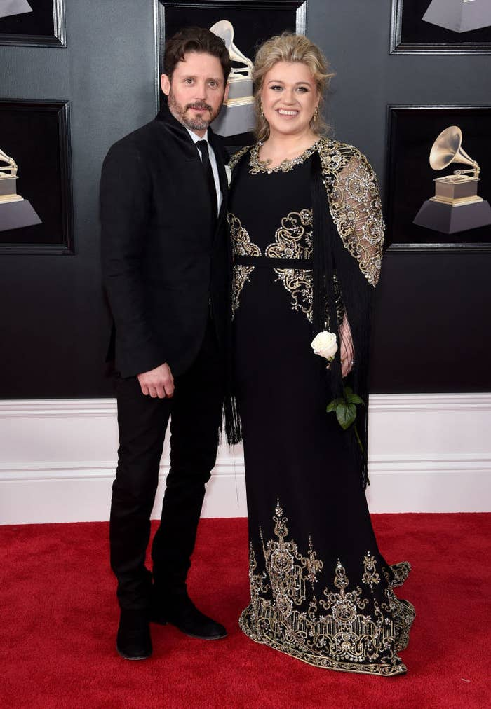 Kelly and Brandon smiling together on a red carpet