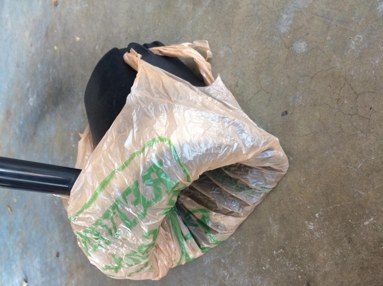 A reviewer's image of the swivel bin and rake pooper scooper with a plastic bag