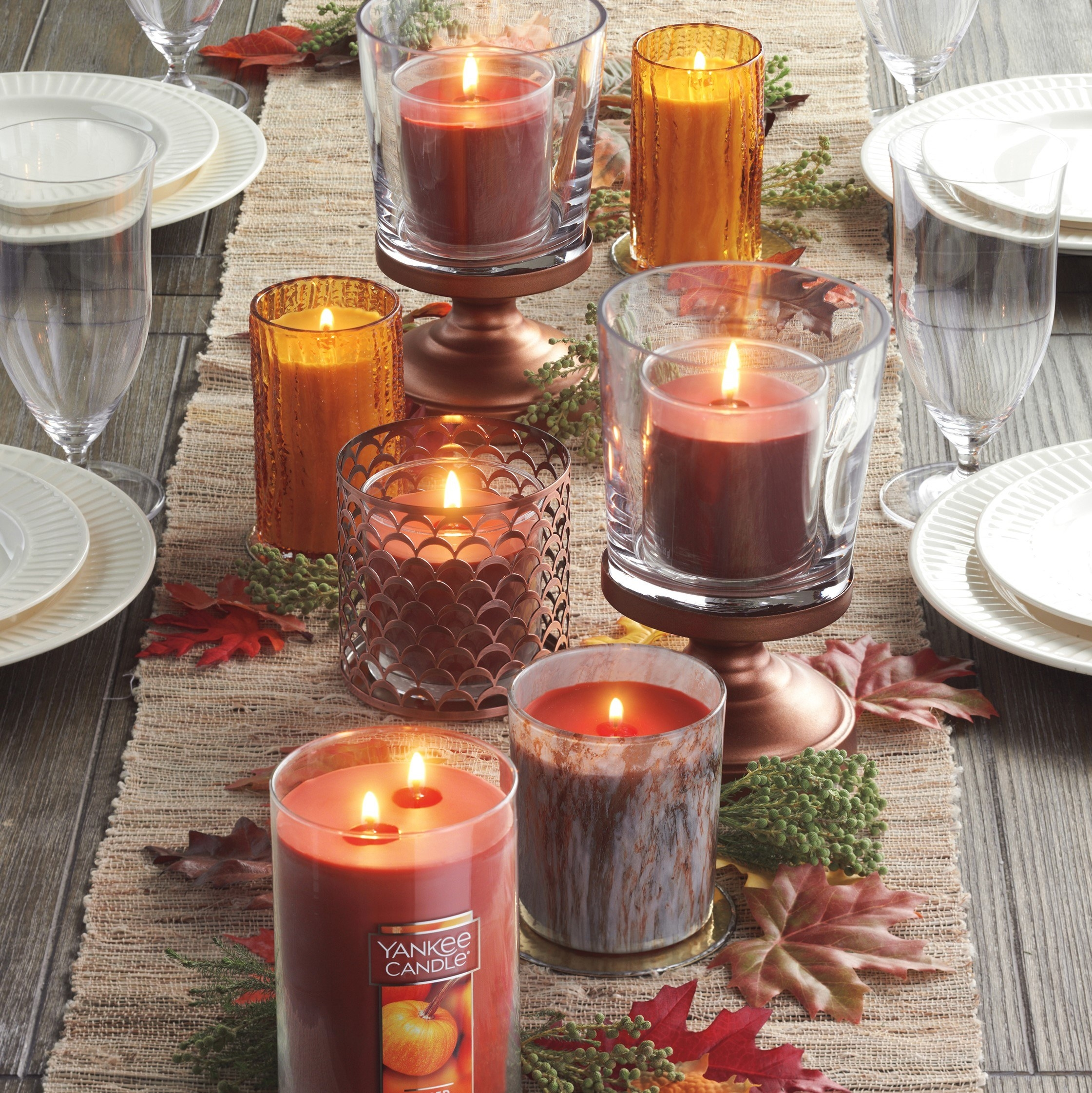 The Yankee Candle featured in multiple sizes on a fall dining table