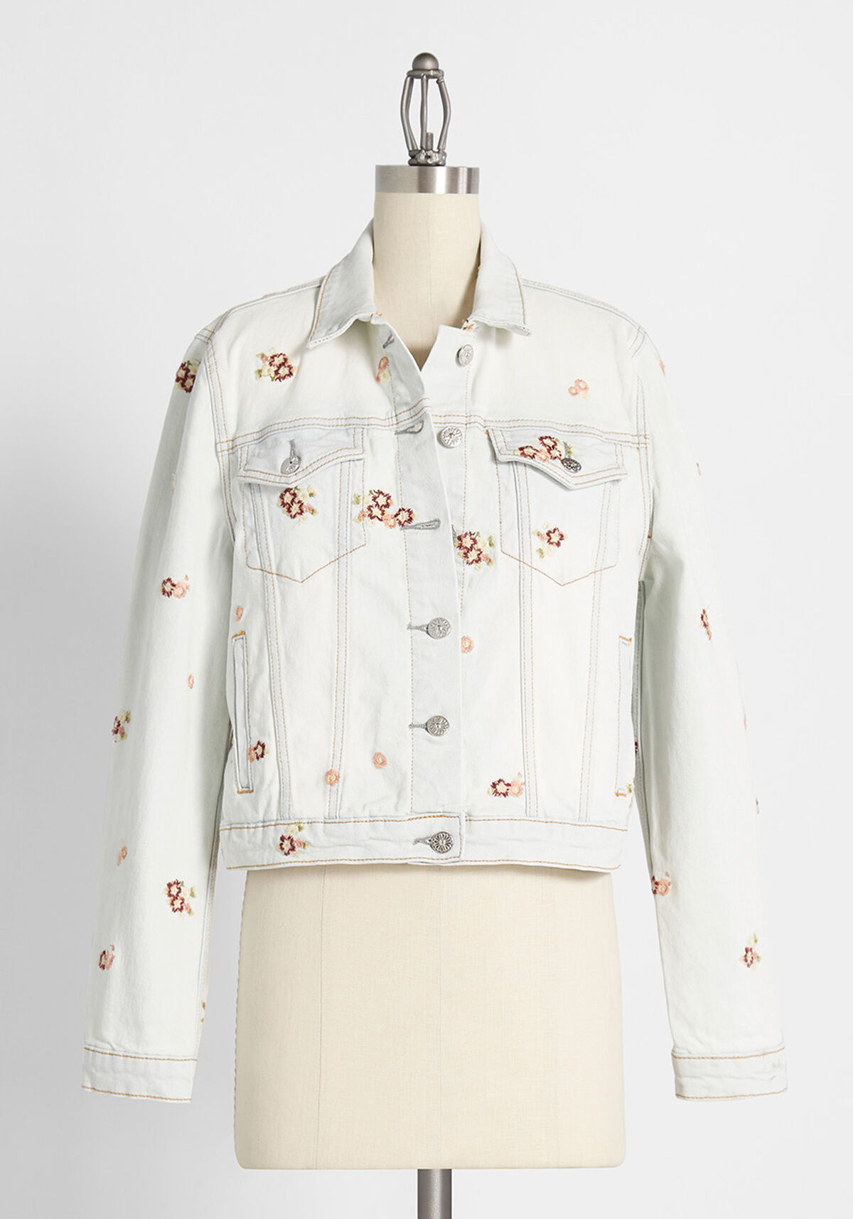 The jacket with a very light-wash style with buttons, two front pockets, and subtle rose embroideries throughout