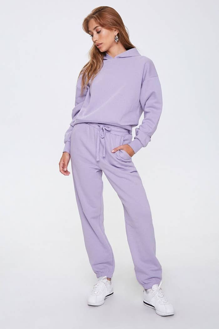 Model wears matching lilac fleece hoodie and joggers set with white sneakers