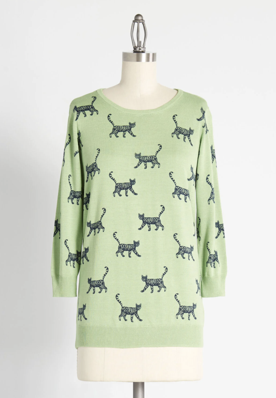 The light green pullover with rows of jungle cats printed on it