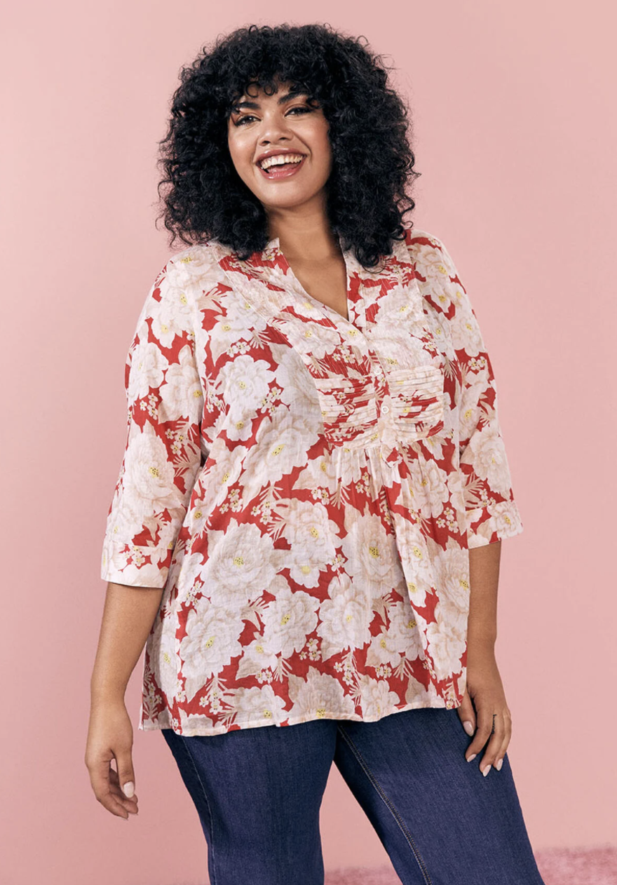 A model wearing the shirt, which has three-quarter sleeves, is red with white roses, and has a tufted style in the middle
