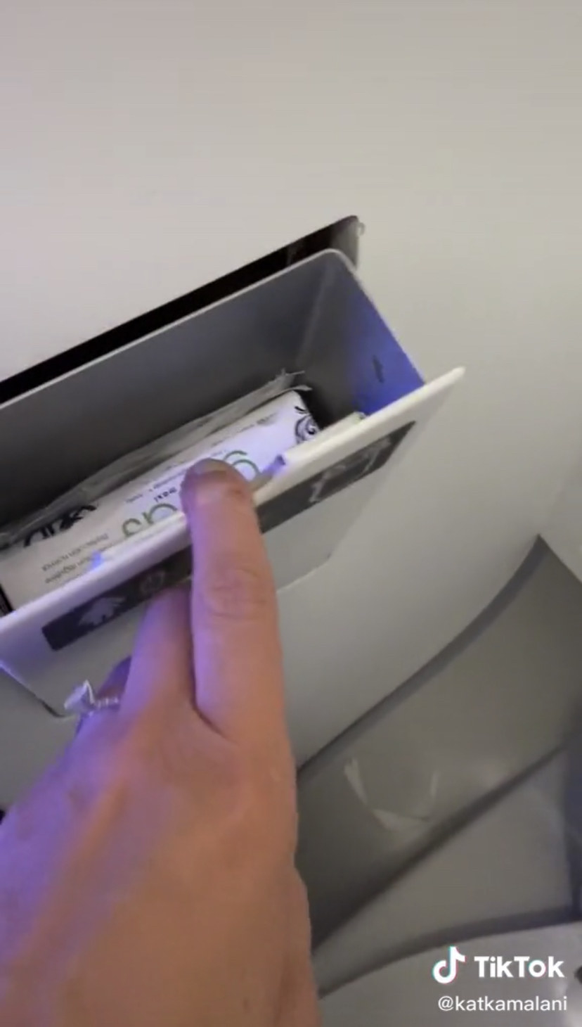 A small compartment in an airplane lavatory being opened to reveal menstrual hygiene products