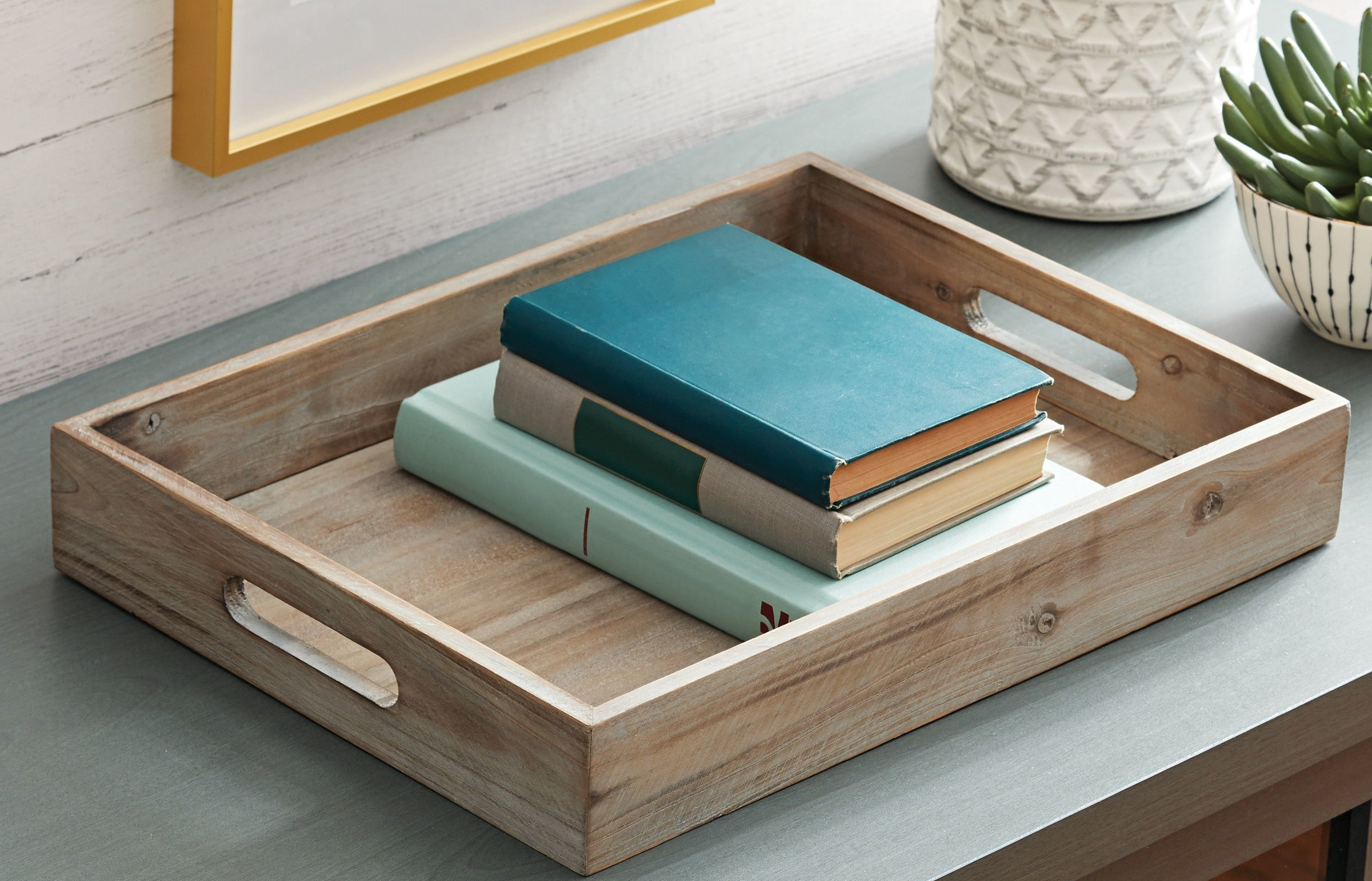 The wooden tray holding some books
