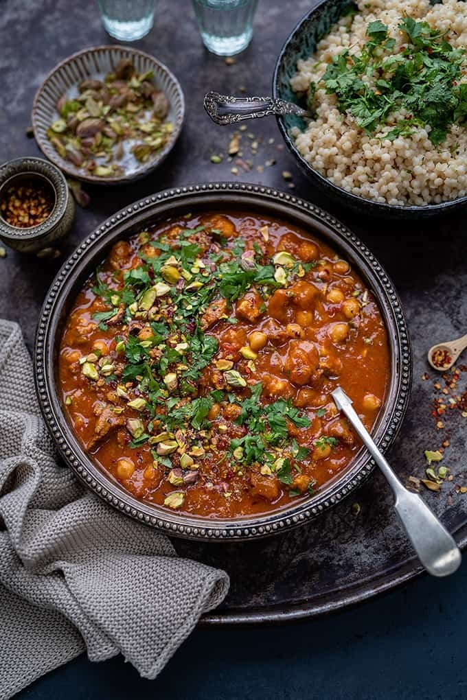 A bowl of Moroccan lamb tagine in a spicy sauce with chickpeas and herbs.
