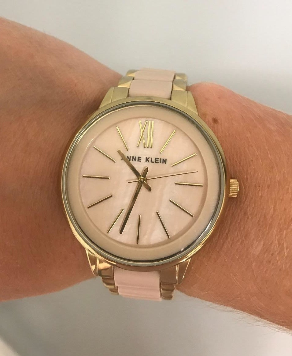 Reviewer wearing the round-face watch in pink and gold