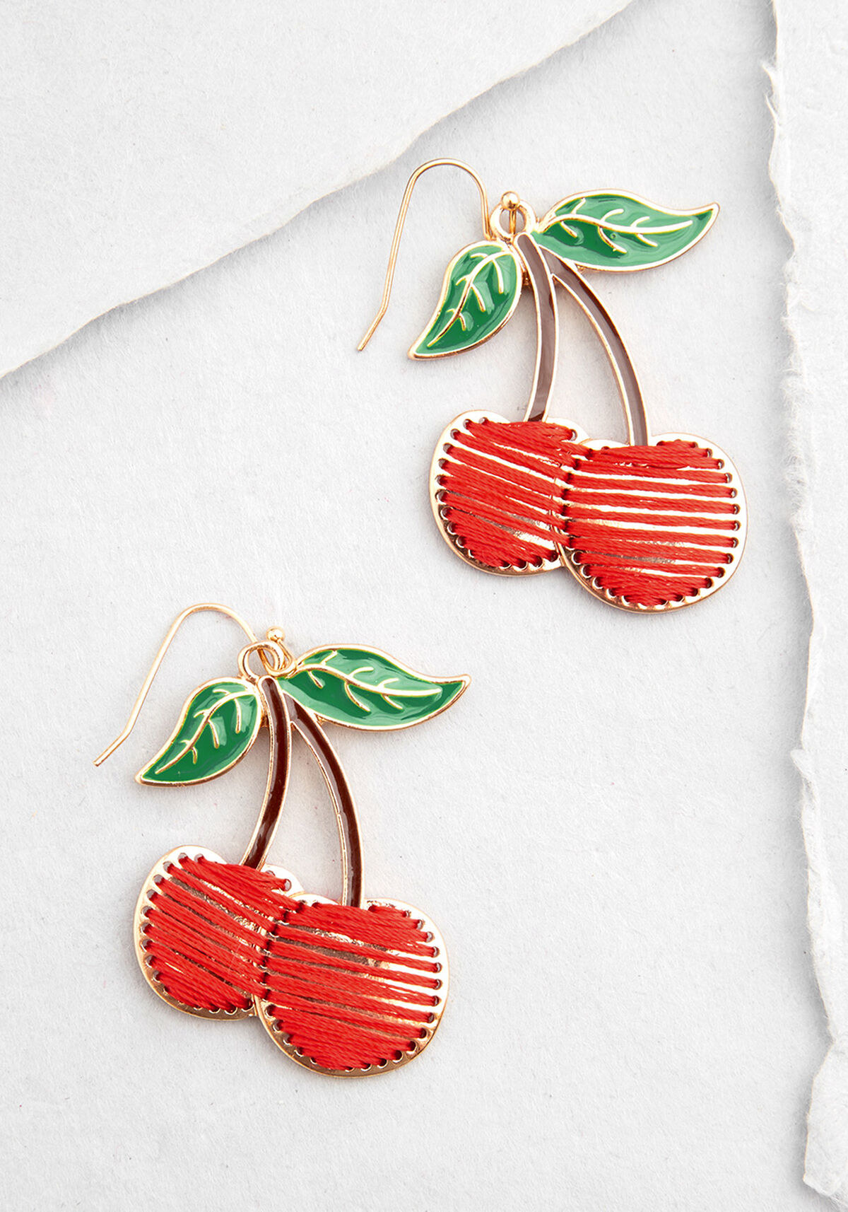 The cherry shaped gold earrings with two cherries per ear, green enameled leaves, brown enameled stems, and fruits that are gold in the back but embroidered with red thread
