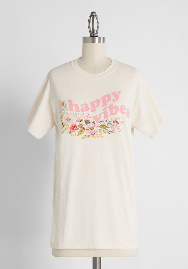 "The white t-shirt that says ""happy vibes"" and has pink flowers on it"