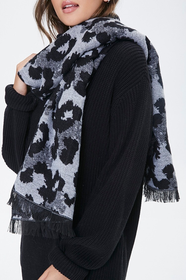 Model wears white, black, and gray leopard-print scarf with cozy black sweater