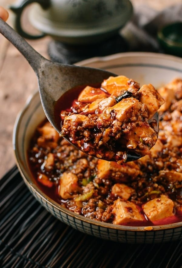 A spoon taking a scoop of Mapo tofu with ground pork.