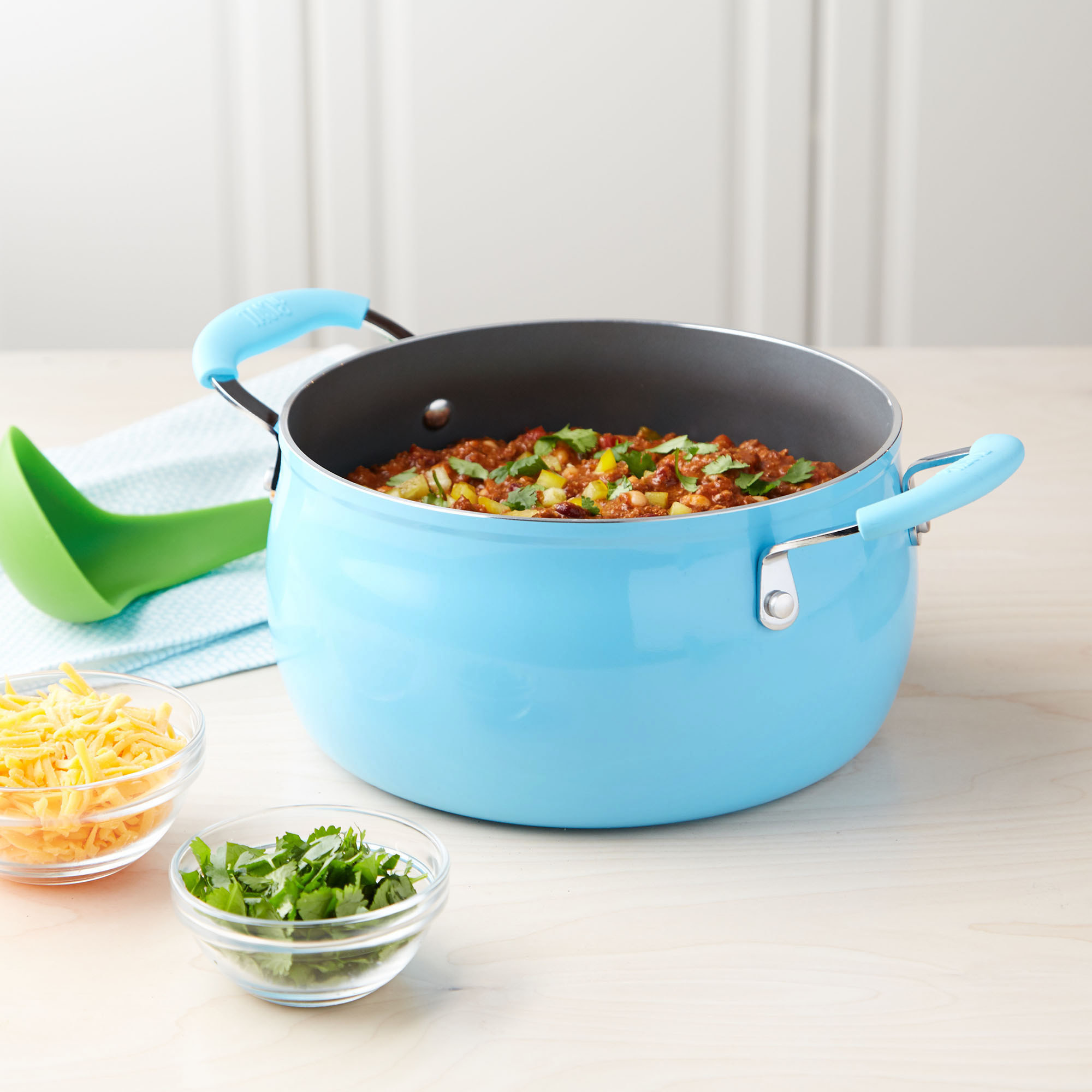 The dutch oven in turquoise filled with chili to show its cooking functionality