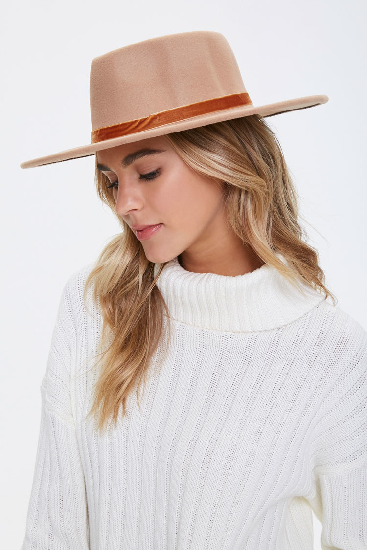 Model wears tan fedora hat with a white cable knit sweater