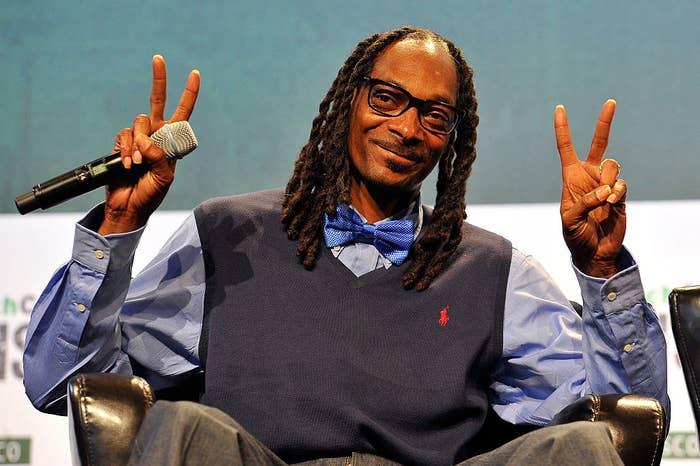 Snoop throwing up two peace signs