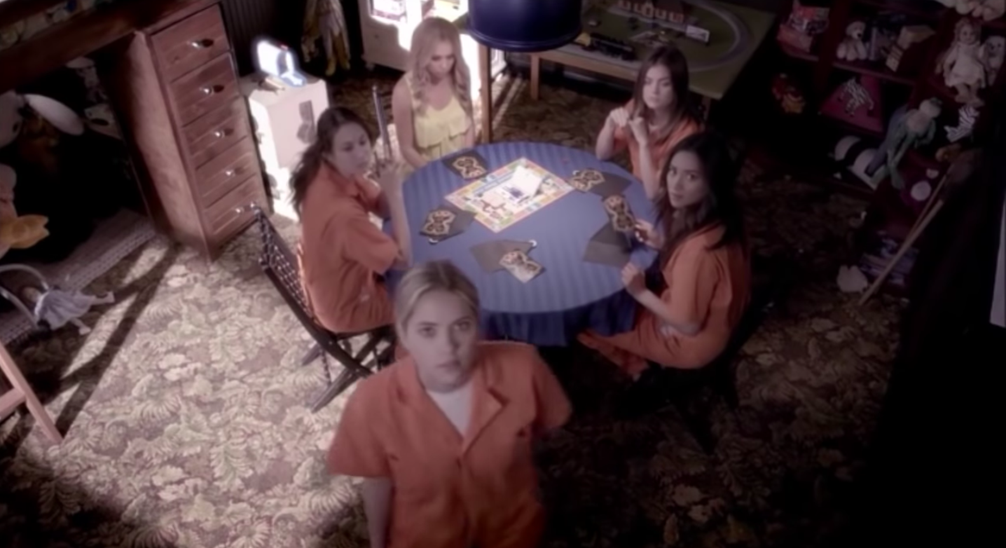 Hanna, Mona, Aria, Spencer, and Emily looking at the camera A set up in the dollhouse.