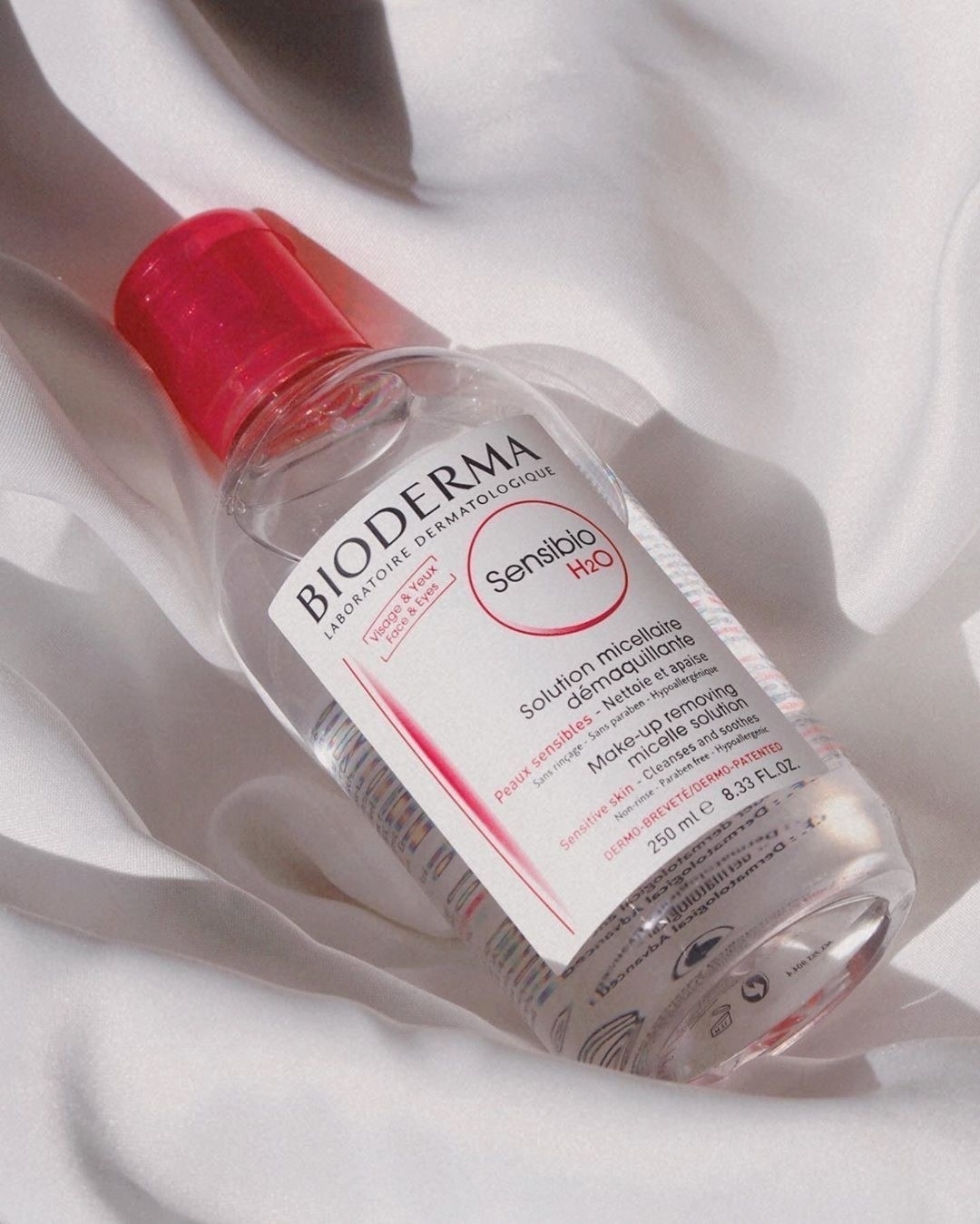 Clear bottle of Bioderma cleansing water on a white pillow