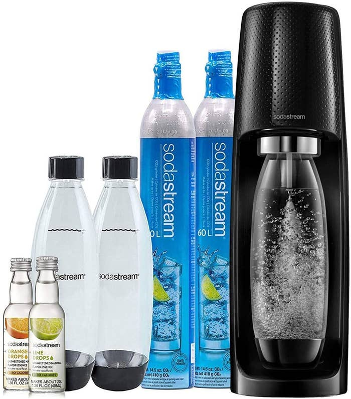 The SodaStream machine, two Co2 canisters, two clear bottles and a lime and orange flavor drops