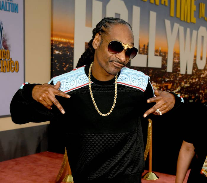 Snoop wearing sunglasses and a chain and holding up two peace signs