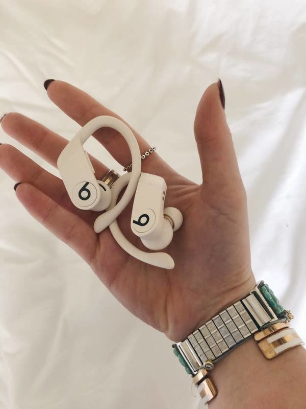 buzzfeed editor holding two in-ear wireless headphones with over-ear hooks