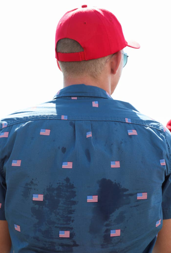 A Trump supporter wears a blue, sweat-stained shirt decorated with American flags